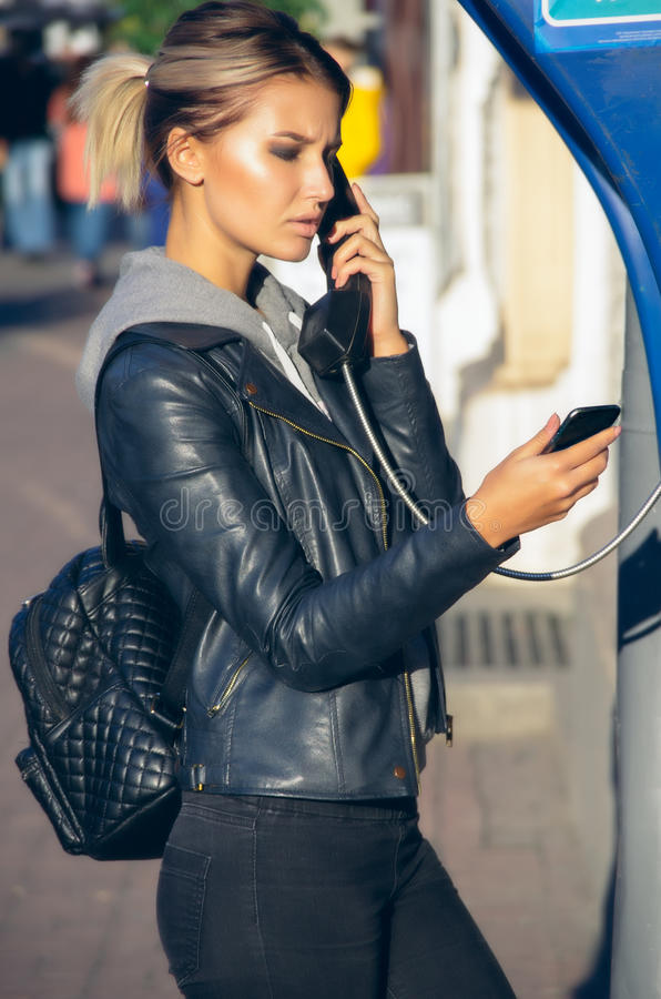 Public phone box. Teenaged girl talking on the telephone on a public phone booth while cheking message on a smartphone stock images