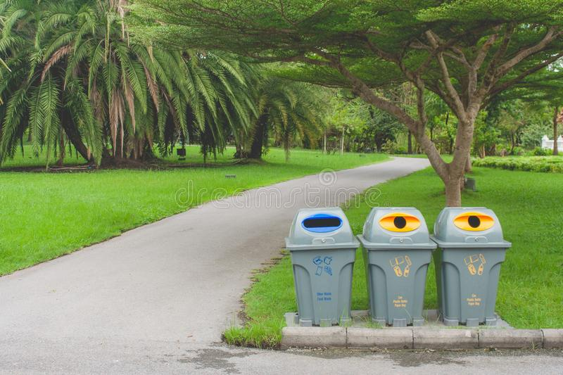 Public recycle bins or segregated waste bins sitting on concrete floor beside walkway in public park. stock photos