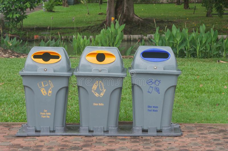 Public recycle bins or segregated waste bins located on concrete floor beside walkway in public park. stock photos