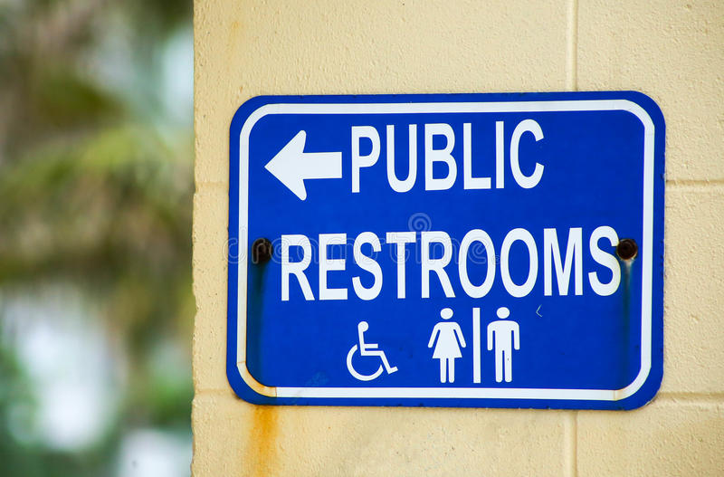 Public Restrooms. A weathered outdoor sign leading visitors to public restrooms stock images