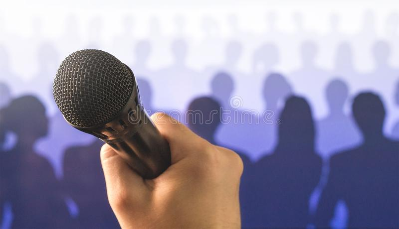 Public speaking and giving speech concept. Close up of hand holding microphone in front of a crowd of silhouette people. Singing to mic in karaoke or talent royalty free stock photos
