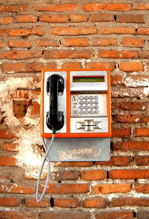 Public telephone. Orange public telephone on a red brick wall royalty free stock photo