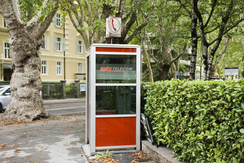 Public telephone on pathway beside traffic road in small alley royalty free stock photos