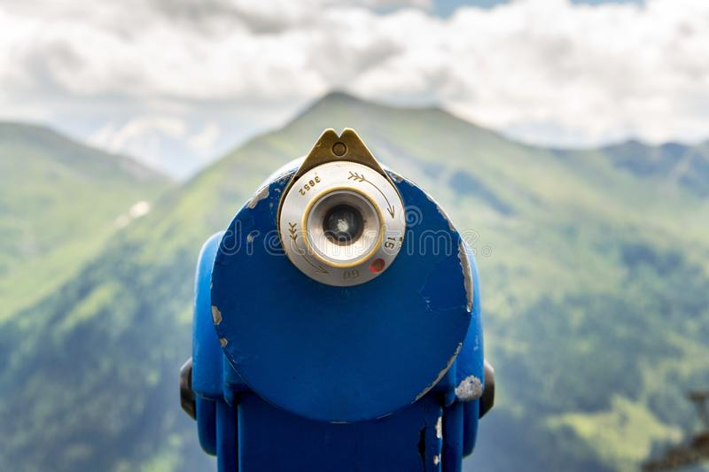 Public telescope arrayed against mountain range Alps in Austria, cloudy summer day. Public blue telescope arrayed against mountain range in Alps, Austria, cloudy stock images