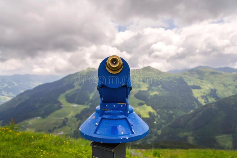 Public telescope arrayed against mountain range Alps in Austria, cloudy summer day. Public blue telescope arrayed against mountain range in Alps, Austria, cloudy royalty free stock image