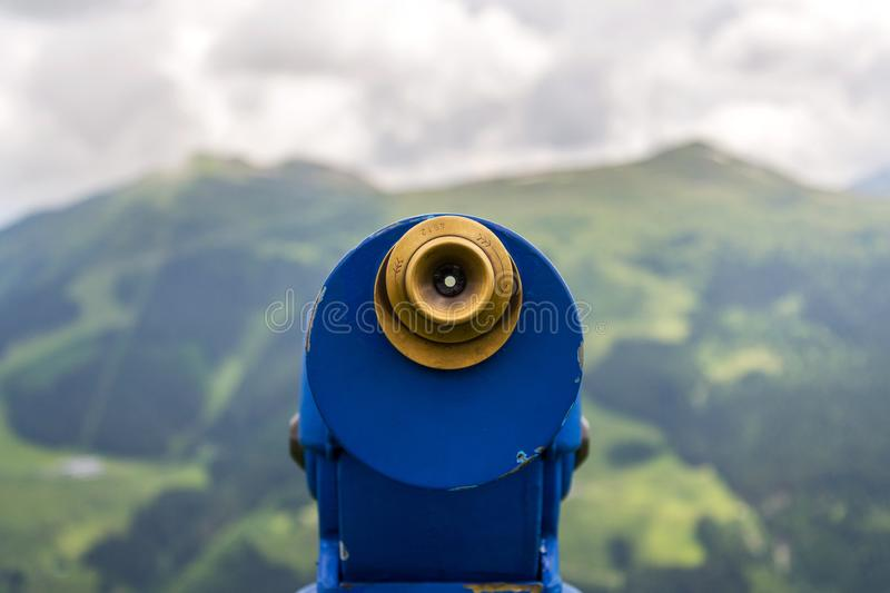 Public telescope arrayed against mountain range Alps in Austria, cloudy summer day. Public blue telescope arrayed against mountain range in Alps, Austria, cloudy stock photography