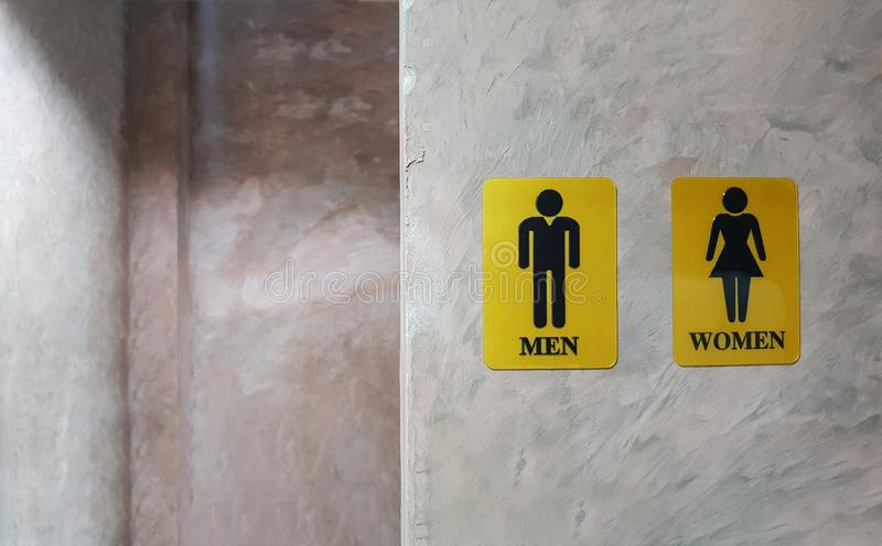 Public toilet of men and women. Sign of lady and gentleman washroom called wc. Mixed gender symbol toilet and restroom behind con stock images