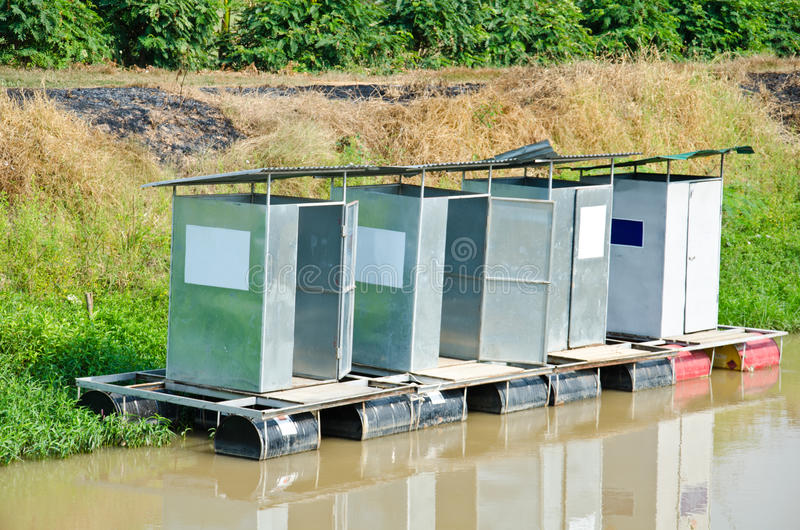 Public toilets float. Public toilets float on the water during a flood stock image