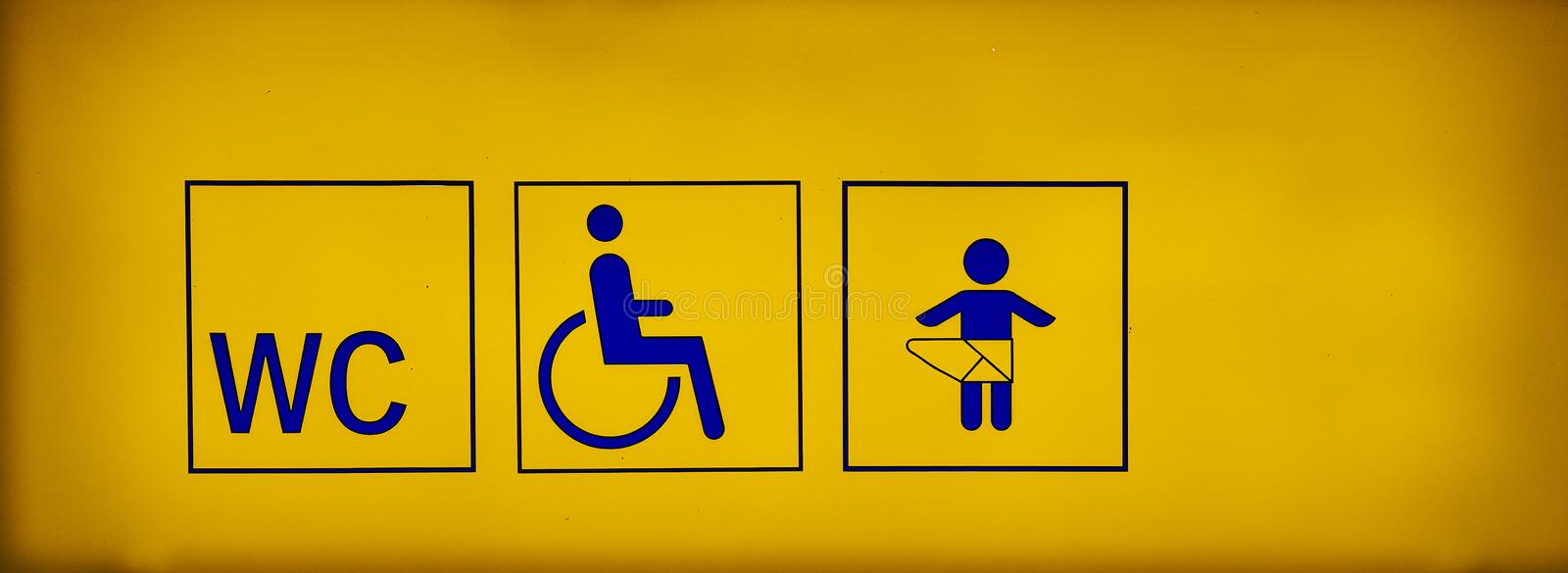 Public toilets signs with a handicapped accessible symbol and baby changing room on yellow neon sign stock photography