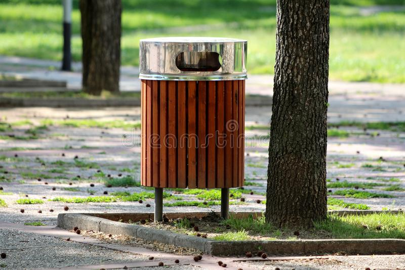 Public trash can made of narrow wooden boards with shiny metal top cover next to old tall tree surrounded with stone tiles in stock photos