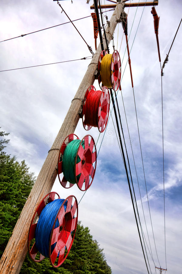 Public Utility Pole Wire Line Upgrade Installation. Spools with color nylon pull ropes hanging on a public utility wood pole carrying electric wires along stock photography