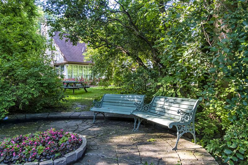 Public wood bench Nice quiet place. Public wood bench in front of old buiding royalty free stock photos