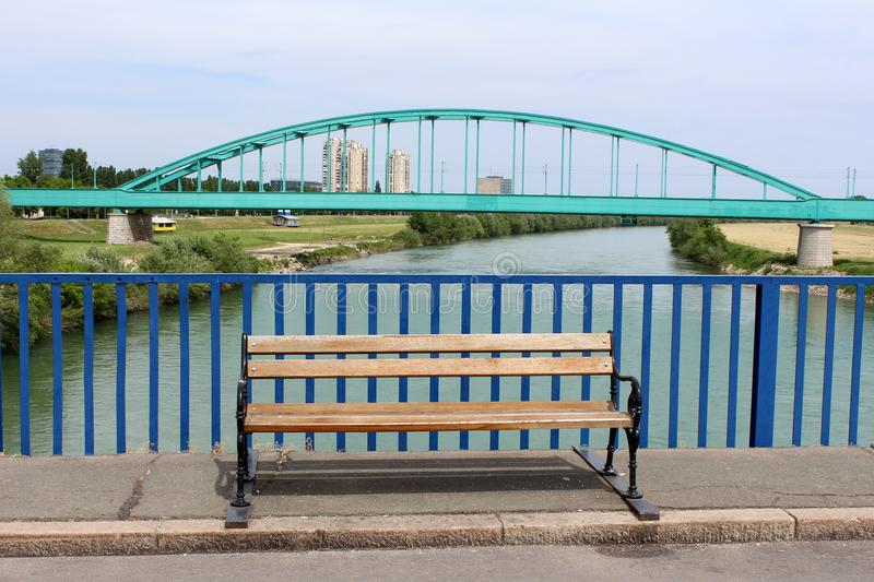 Public wooden bench with wrought iron legs and old metal arched railway bridge in background royalty free stock photography