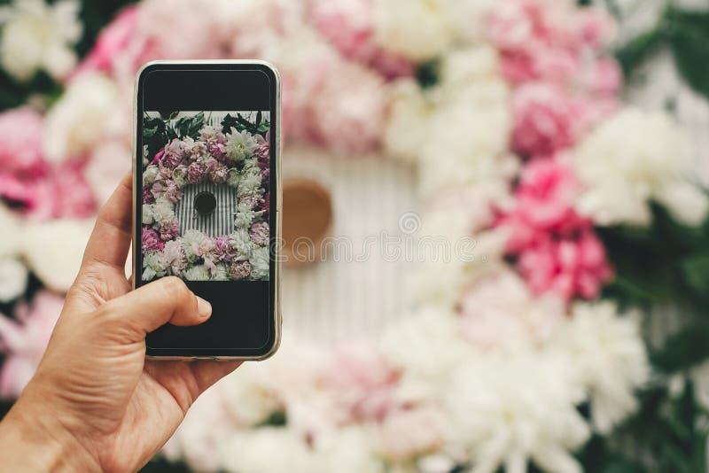 Publicar em blogs e oficina de Instagram O telefone da terra arrendada da mão e a foto da tomada da bebida do café em peônias cor fotografia de stock