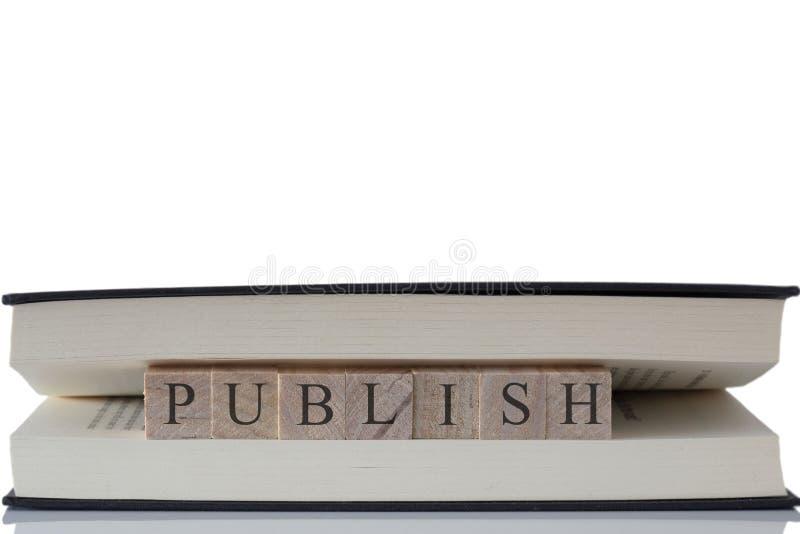 Publiceer geschreven op houten blokken binnen een boek dat op een witte achtergrond wordt geïsoleerd stock foto's