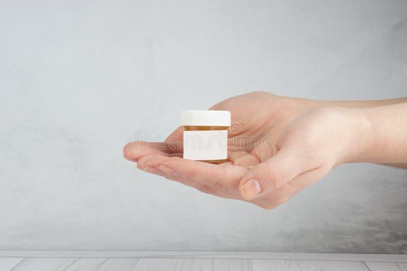 Publicidad de un producto cosmético, manos femeninas aseadas que sostienen un tarro con un cosmético foto de archivo