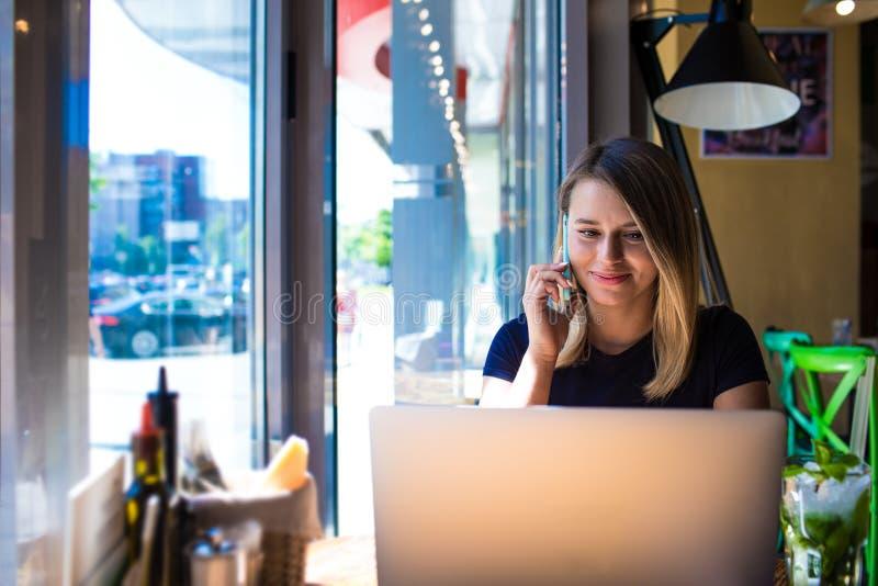 Publicista profesional de la mujer que habla en el teléfono móvil con el cliente y que lee la información en el ordenador portáti foto de archivo libre de regalías