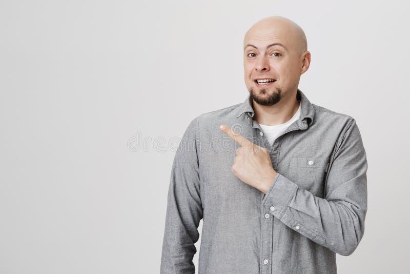 Publicité, émotions et concept de langage du corps Jeune homme chauve attirant avec le point de barbe son doigt loin au-dessus de photo libre de droits