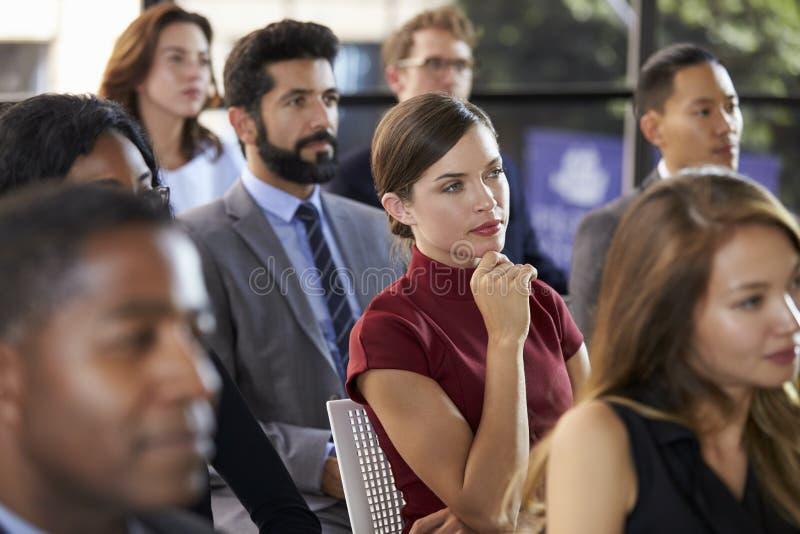 Publiek bij een bedrijfsseminarie die aan een spreker luisteren stock foto