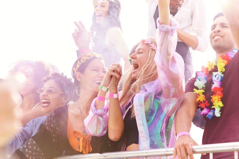 Publiek met gekleurde rook achter het dansen en zingen van een barrière op het openluchtfestival dat muziek leuk vindt stock afbeeldingen
