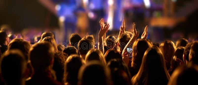 Publiek met handen bij een muziekfestival en lichten worden opgeheven die neer van boven het stadium stromen dat royalty-vrije stock afbeeldingen
