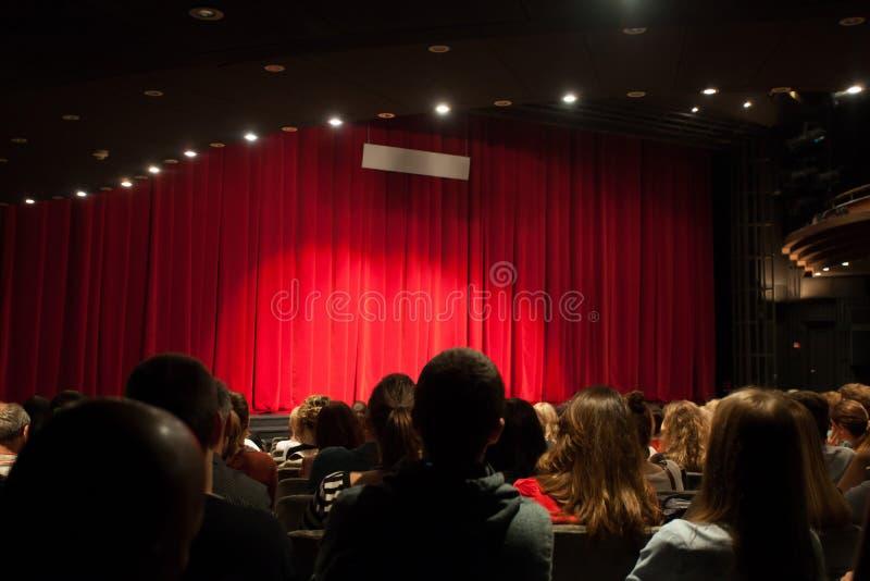 Publiek in theater die op spel wachten om te beginnen stock afbeelding