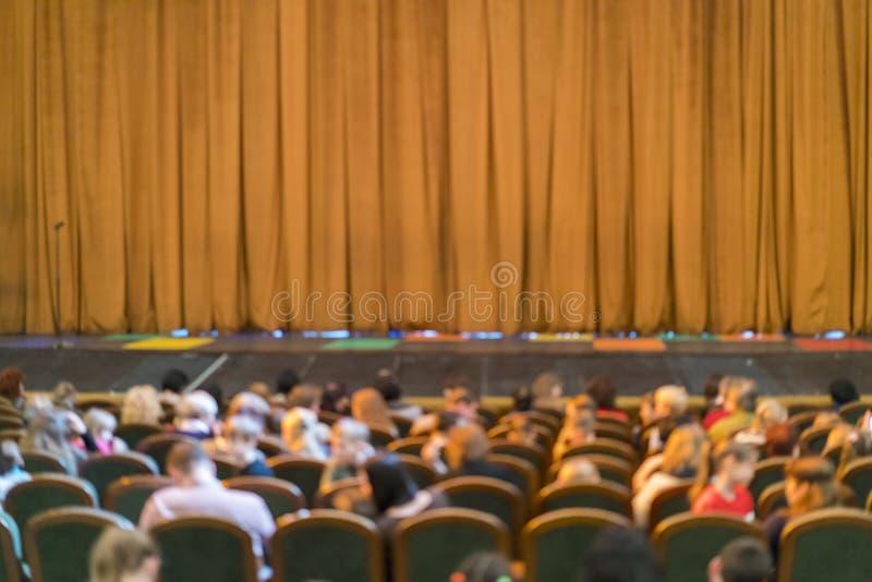 Publiek in Theater gesloten stadiumgordijn in een theater onscherp royalty-vrije stock afbeeldingen
