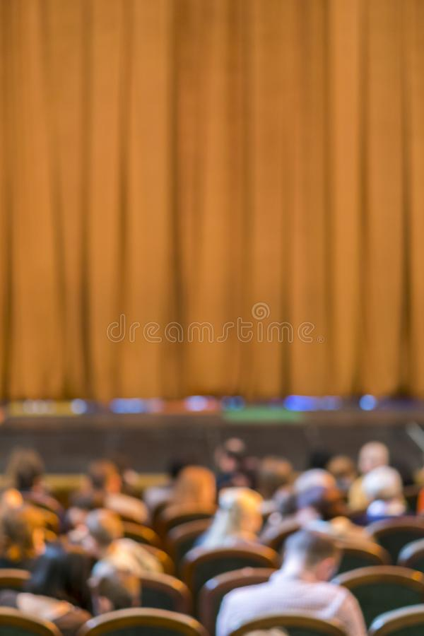 Publiek in Theater gesloten stadiumgordijn in een theater onscherp Verticale foto stock afbeelding