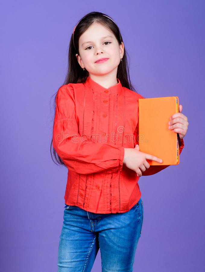 Published information. Small child holding book with orange cover for vital information. Little girl with information. Materials. Information from reliable royalty free stock photography