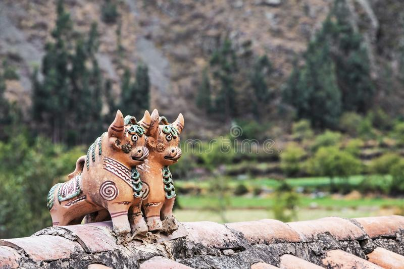 Pucara`s bulls peruvian fertility icon on the roof of a andes mountain house. Pucara`s bulls peruvian culture lucky icon on the roof of a house with andes royalty free stock photography