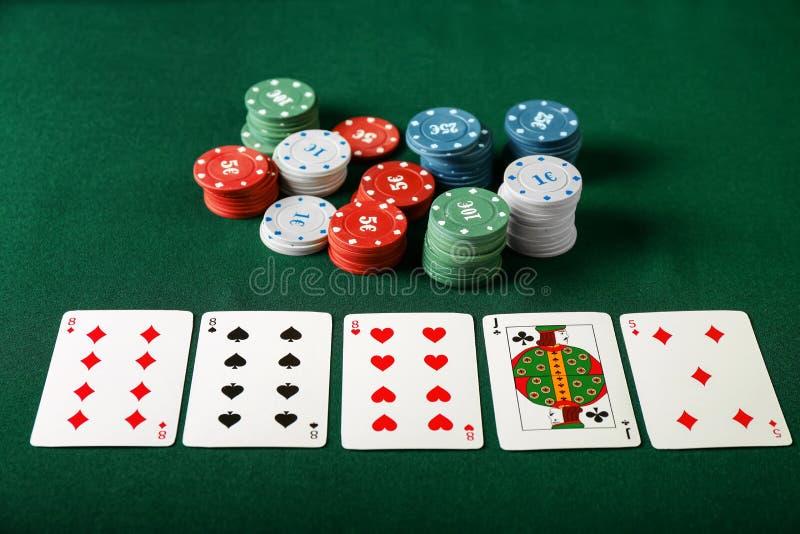 Puces avec des cartes pour le jeu de poker sur la table verte image stock