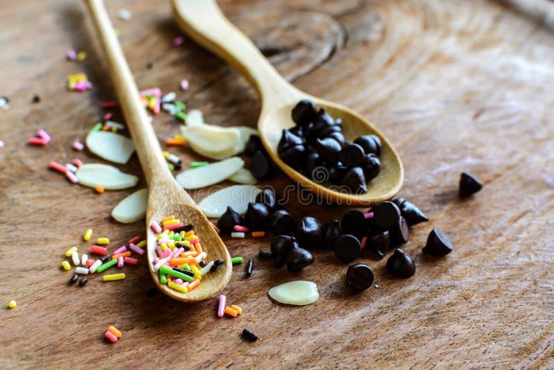 Puces de chocolat sur la cuillère et les ingrédients en bois pour la cuisson photographie stock libre de droits