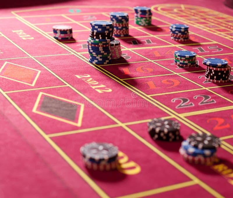 Puces de jeu sur la table rouge de roulette photos stock