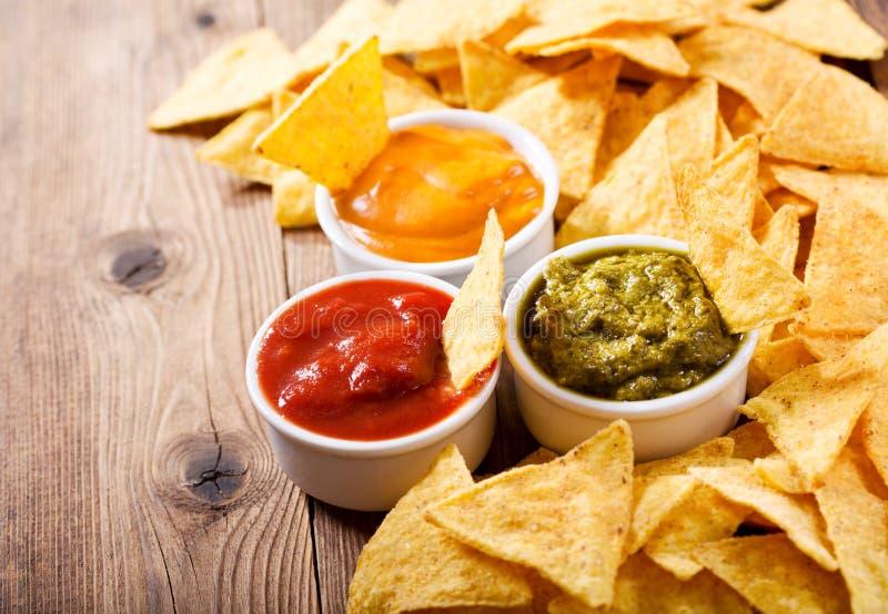 Puces de maïs mexicaines de nachos avec l'immersion de guacamole, de Salsa et de fromage images stock