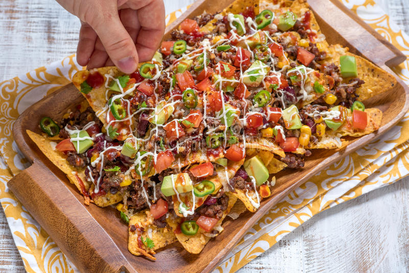 Puces de tortilla de maïs de Nacho avec du fromage, la viande, le guacamole et le Salsa épicé d'un rouge ardent photo libre de droits