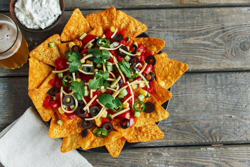 Puces de tortilla mexicaines avec de la sauce au poivre à olives noires de tomate de fromage photographie stock