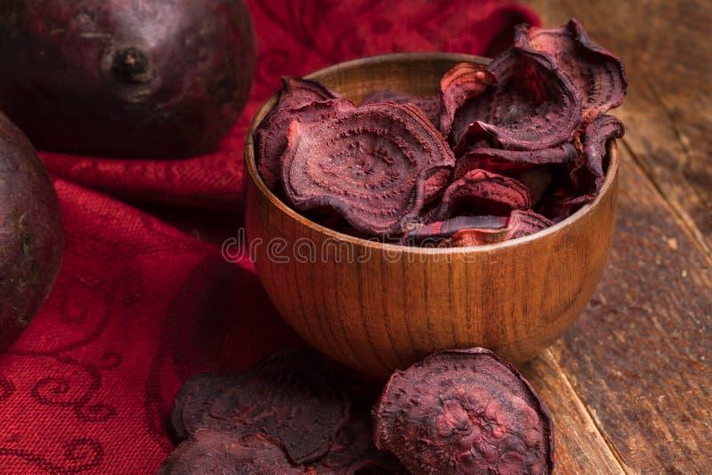 Puces en gros plan de betteraves en cuvette en bois et betteraves entières sur la serviette rouge sur la vieille table en bois photos libres de droits