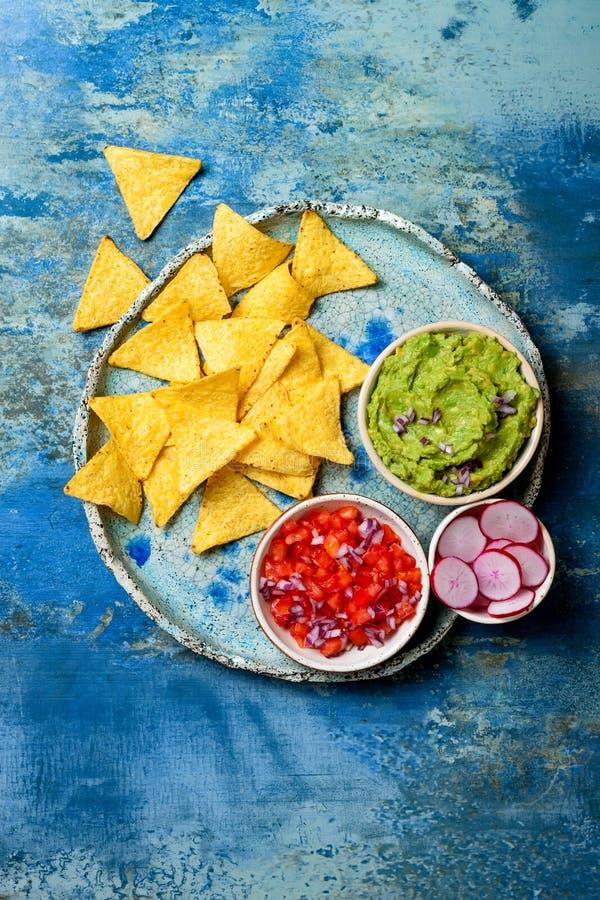 Puces jaunes de nachos de maïs avec l'immersion de guacamole, le Salsa de tomate et les radis au-dessus du plat bleu sur le fond photos libres de droits