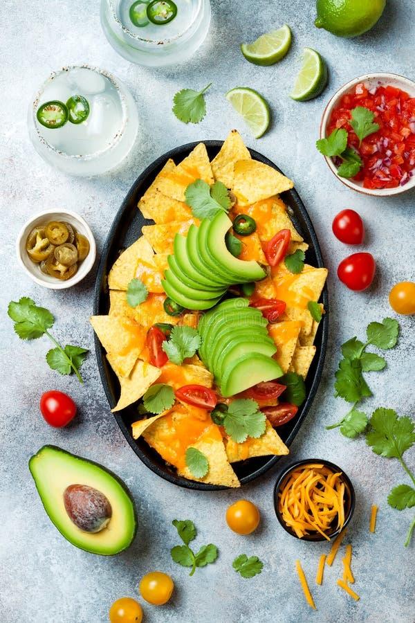 Puces jaunes de nachos de maïs avec de la sauce au fromage fondue, l'avocat, le jalapeno, les feuilles de cilantro, le Salsa de  image libre de droits