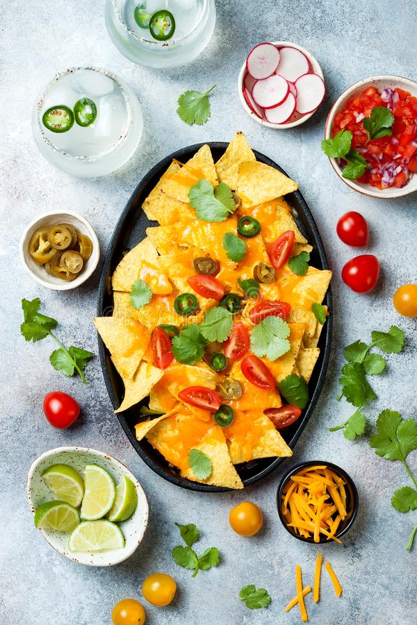 Puces jaunes de nachos de maïs avec de la sauce au fromage fondue, l'avocat, le jalapeno, les feuilles de cilantro, le Salsa de  photos stock