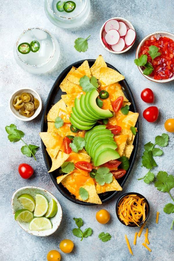 Puces jaunes de nachos de maïs avec de la sauce au fromage fondue, l'avocat, le jalapeno, les feuilles de cilantro, le Salsa de  photographie stock