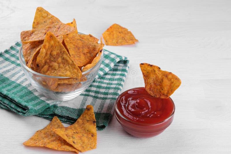 Puces Nachos dans une cuvette avec de la sauce rouge sur une table en bois blanche casse-croûte images libres de droits