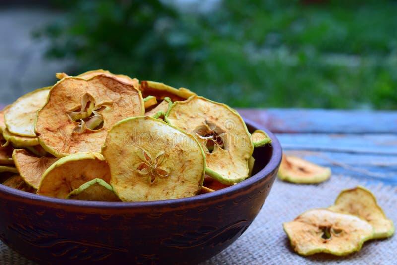 Puces organiques de pomme Fruits secs Casse-croûte doux sain Nourriture déshydratée et crue Copiez l'espace photos stock