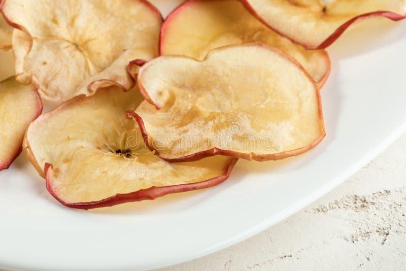 Puces s?ches naturelles en gros plan de pomme du plat blanc images stock