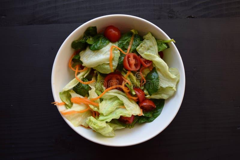 Puchar świeża zielona sałatka, pomidory, ogórek na drewno stole przeciw ciemnemu tłu z solą, oliwka, słonecznikowy olej, pieprz obraz stock