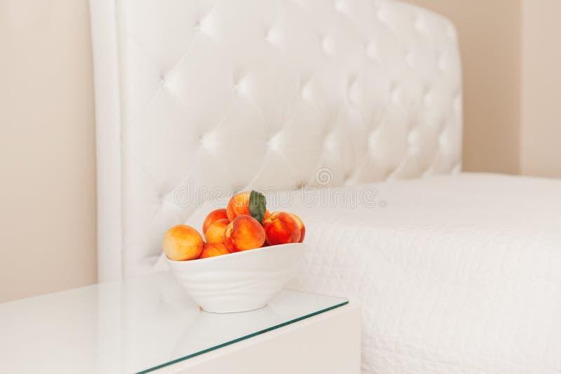 Puchar świeże słodkie dojrzałe owoc brzoskwinie na stołowym pobliskim pustym białym łóżku obraz stock