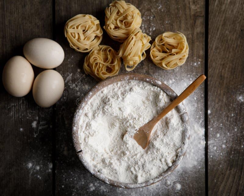 Puchar biała mąka, jajka i makaron na białym drewnianym stole, odgórny v zdjęcie stock