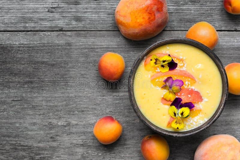 Puchar domowej roboty żółty smoothie z świeżym mango, brzoskwiniami i morelami, zdjęcia stock