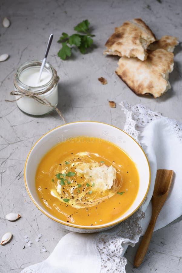 Puchar dyniowego curry'ego kremowa polewka na stole, słuzyć z chlebem obraz royalty free