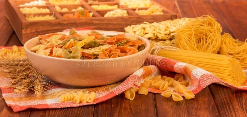 Puchar farfalle, wiązka spaghetti, gniazdeczko ciency wermiszel, zdjęcie stock